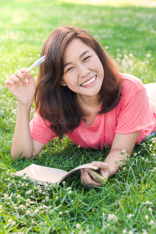 在她的笔记本的美好的年轻亚洲妇女文字在草甸 免版税库存照片