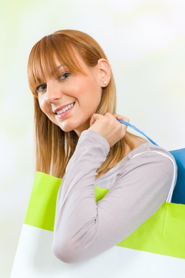 在她的肩膀的少妇运载的购物袋 免版税库存照片