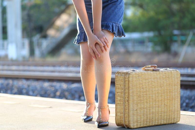 在她的膝盖的特写镜头年轻女人感觉的痛苦在火车站,医疗保健和医学概念 免版税库存照片