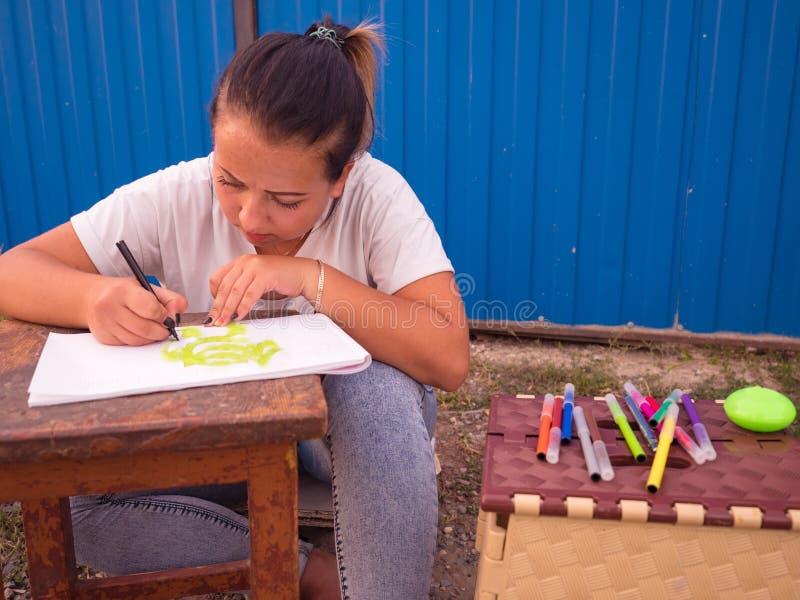 在她的膝盖的青少年的女孩图画 免版税库存照片