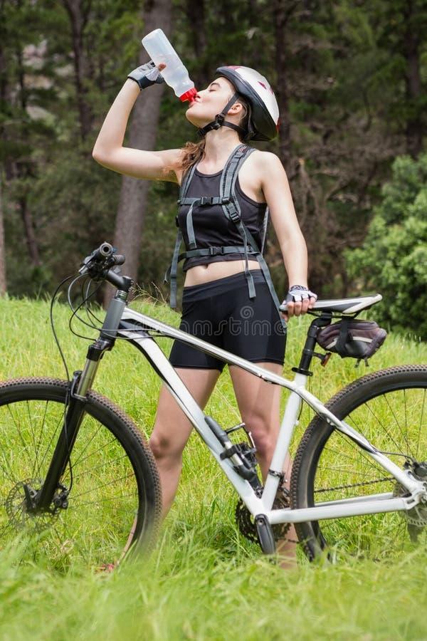 在她的自行车旁边的妇女饮用水 图库摄影