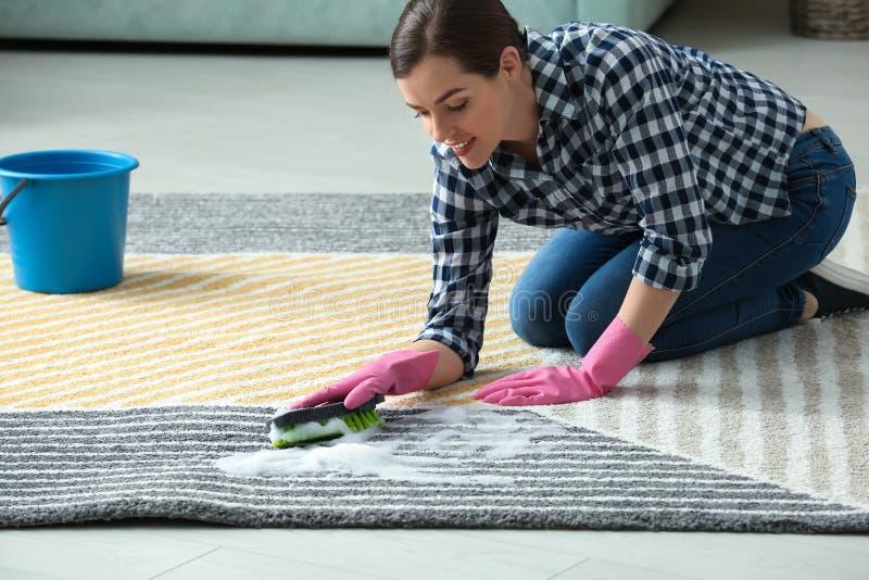 在她的舱内甲板的年轻女人清洗的地毯 库存照片