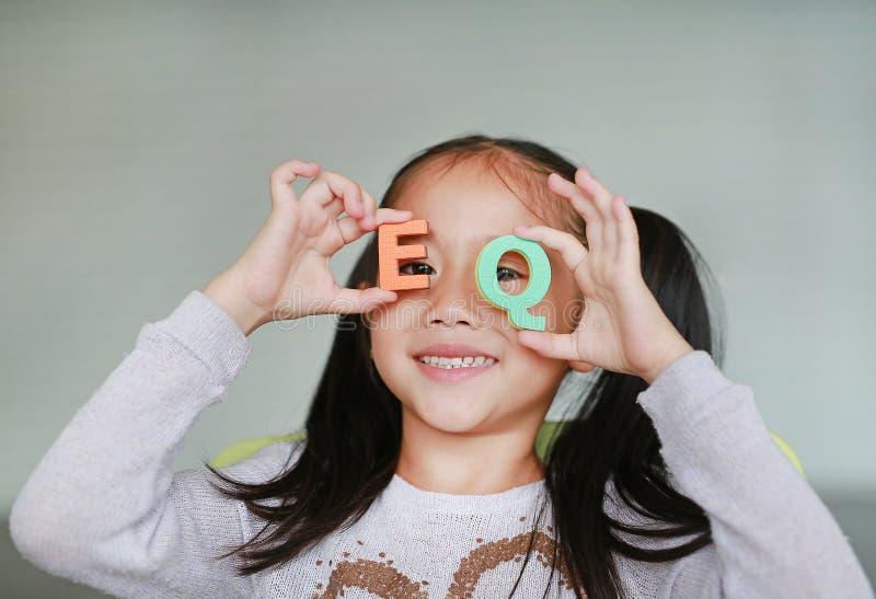 在她的面孔的愉快的矮小的亚洲儿童女孩藏品字母表EQ情感商数文本 r 图库摄影