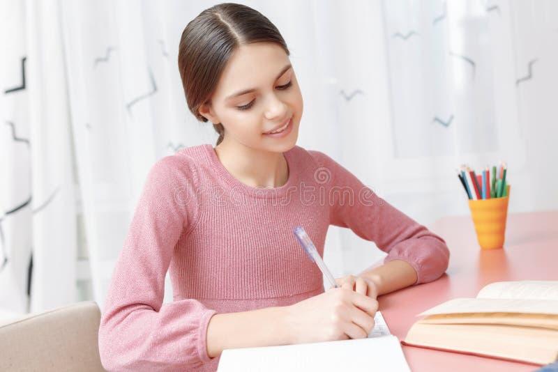 在她的练习本的十几岁的女孩文字 免版税库存图片