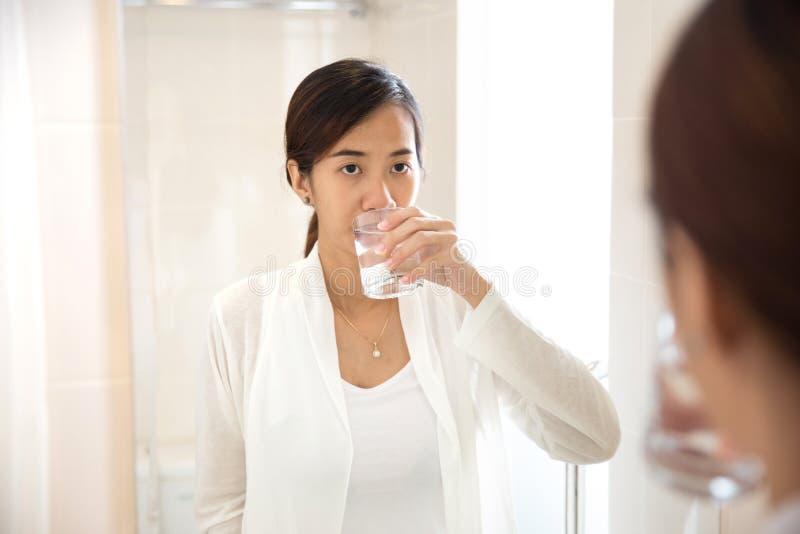在她的嘴的亚洲少妇漱口药在刷牙以后 库存照片