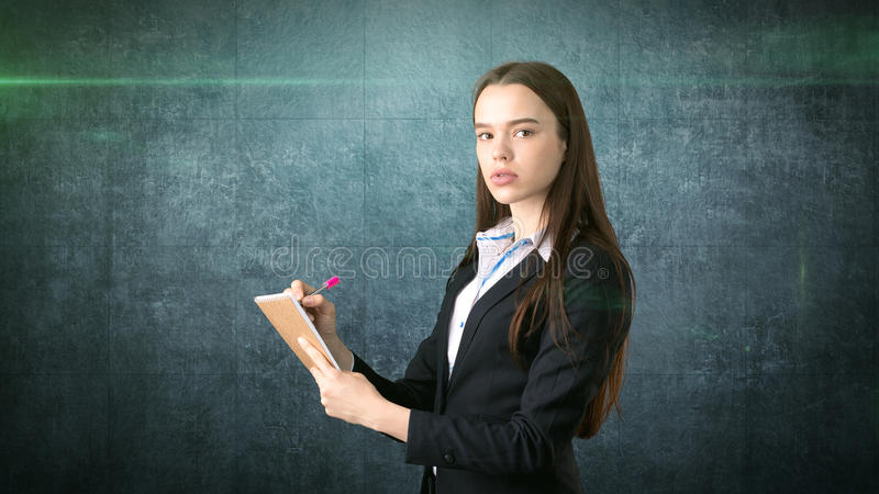 在她的组织者的严肃的确信的女实业家文字演播室背景的 库存照片