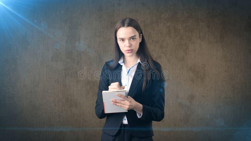 在她的组织者的严肃的确信的女实业家文字演播室背景的 免版税库存照片