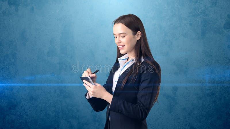 在她的组织者的友好的确信的微笑的女实业家文字演播室背景的 免版税图库摄影