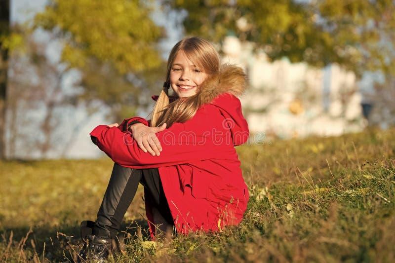 在她自己的样式 保留身体衣服暖和秋天天 秋天成套装备概念 温暖的秋天的外套最佳的选择 孩子女孩 免版税库存图片
