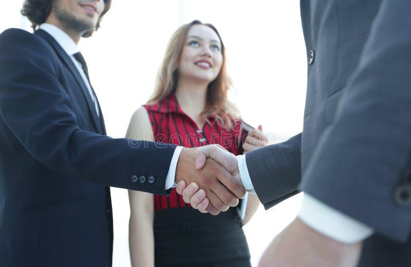 在好成交以后的商人握手 到达天空的企业概念金黄回归键所有权 图库摄影