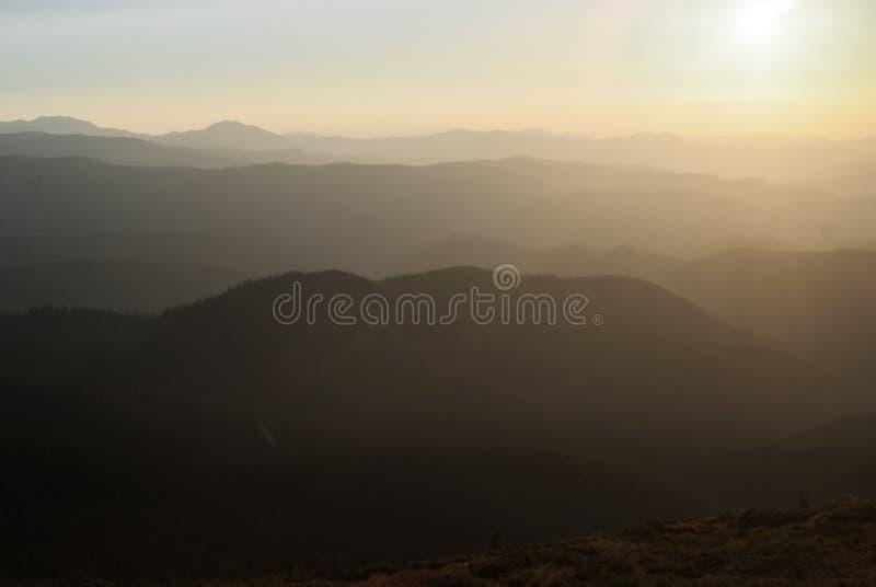 在好日子和日落的山与云彩和具球果森林风景 库存图片