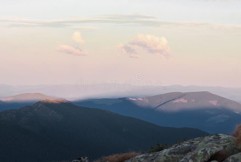 在好日子和日落的山与云彩和具球果森林风景 免版税库存图片