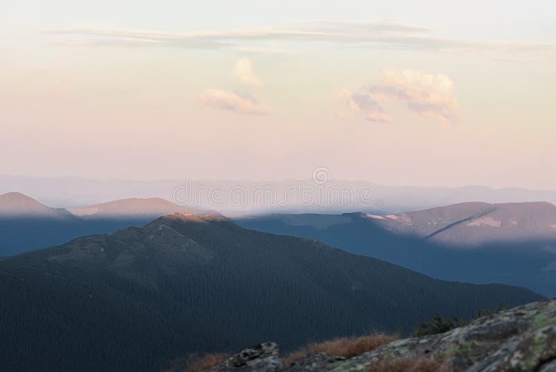 在好日子和日落的山与云彩和具球果森林风景 图库摄影