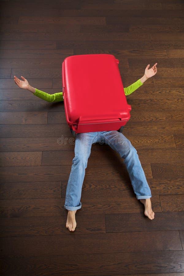 在妇女之下的位于的红色手提箱 库存照片