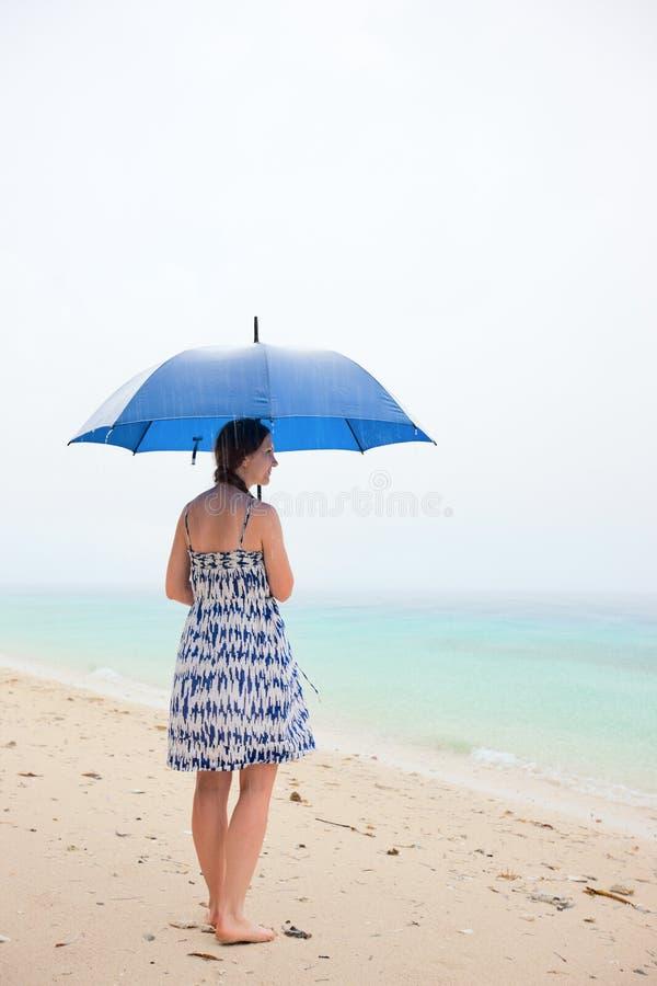 在妇女之下的海滩雨 免版税图库摄影