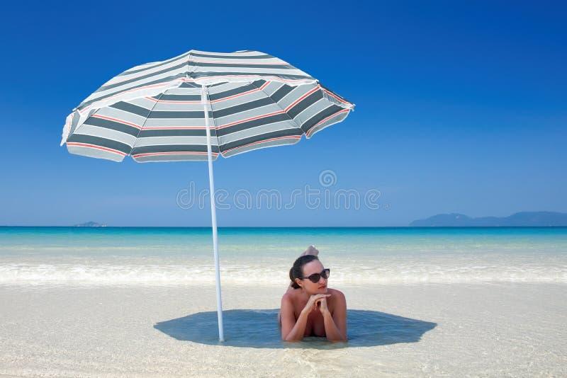 在妇女之下的海滩休息的伞 库存图片