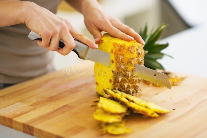 在妇女切口菠萝的特写镜头 免版税库存图片