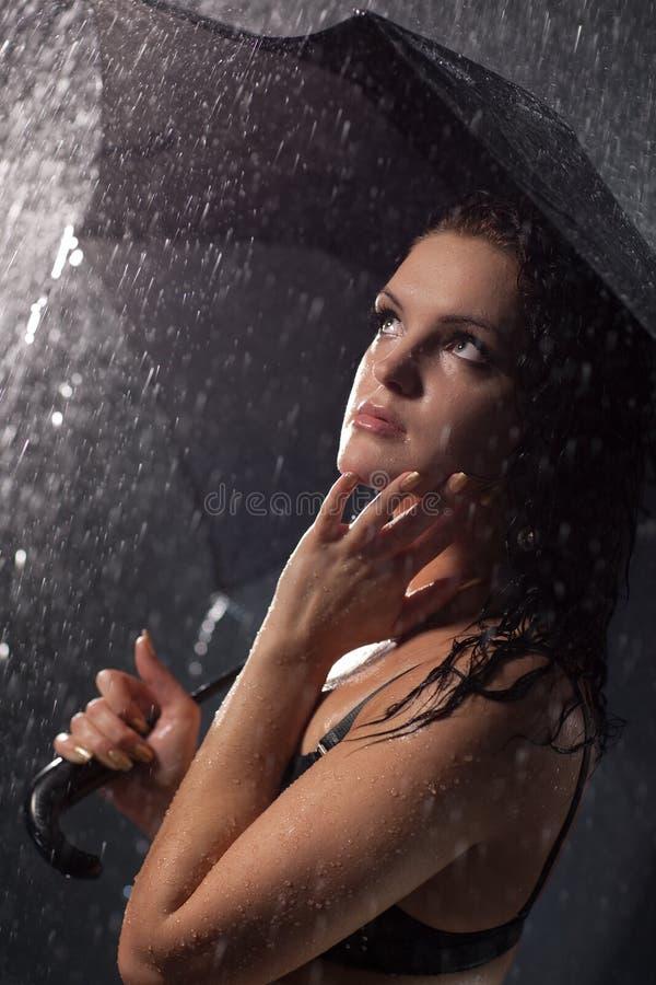 在妇女年轻人之下的雨伞 免版税库存照片