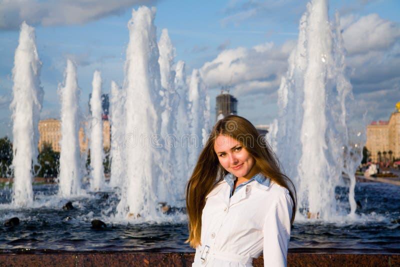 在妇女年轻人附近的喷泉 免版税库存照片