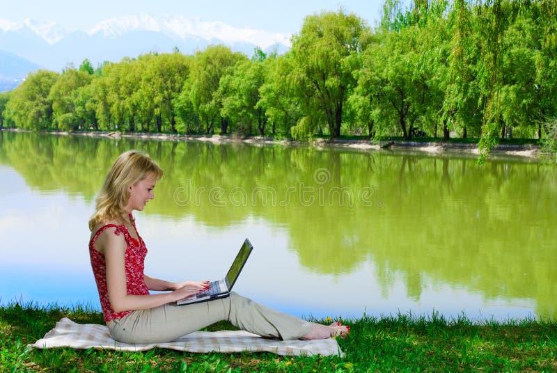 在妇女年轻人附近的美丽的湖膝上型计算机 图库摄影