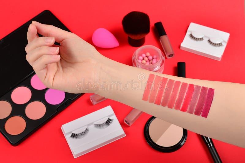 在妇女手上的唇膏样片 与化妆美容品,基础,唇膏,眼影的专业构成产品, 免版税库存图片