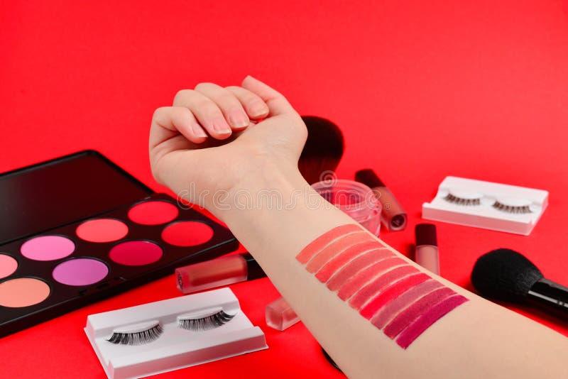 在妇女手上的唇膏样片 与化妆美容品,基础,唇膏,眼影的专业构成产品, 免版税库存照片
