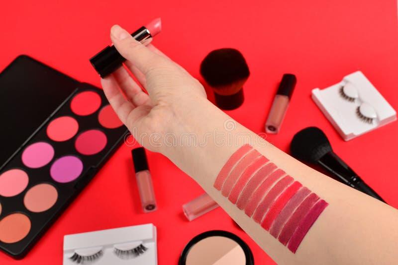 在妇女手上的唇膏样片 与化妆美容品,基础,唇膏,眼影的专业构成产品, 库存照片