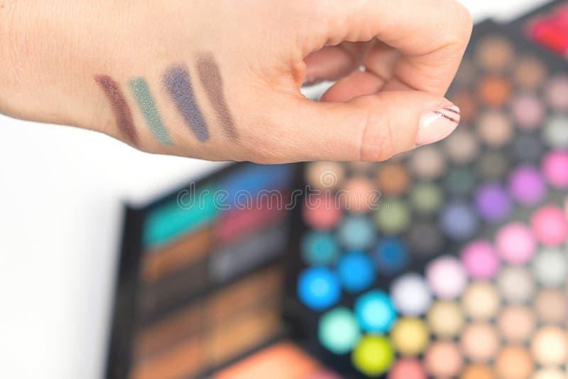 在妇女手上的眼影样片 装饰的化妆用品 库存图片