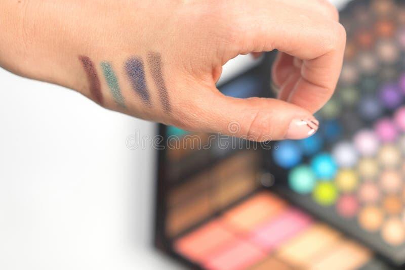 在妇女手上的眼影样片 装饰的化妆用品 库存照片