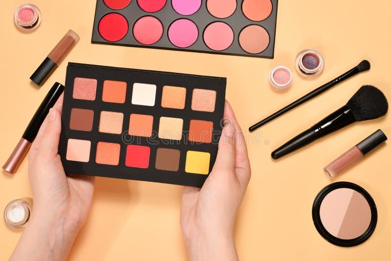 在妇女手上的眼影调色板 与化妆美容品,基础,唇膏,眼影的专业构成产品, 库存图片
