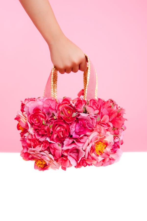 在妇女现有量的红色花袋子在桃红色背景 免版税库存图片