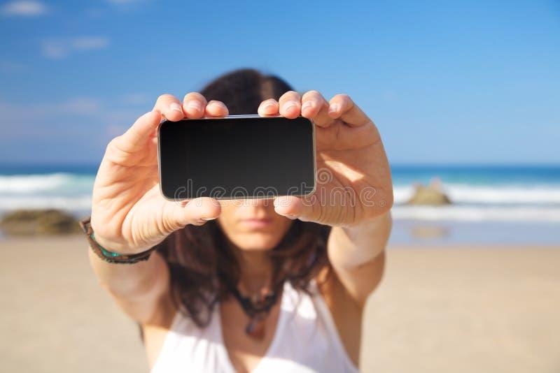 在妇女现有量的黑屏移动电话 免版税库存照片