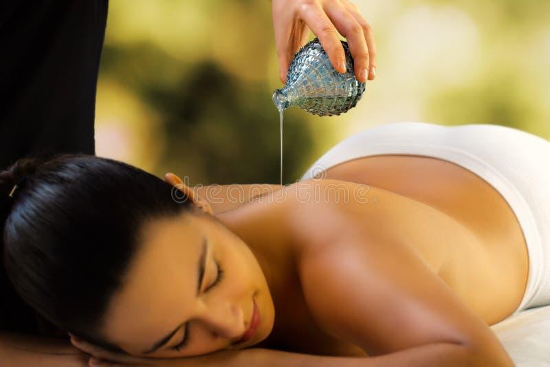 在妇女的后面的治疗师倾吐的按摩油 免版税库存图片