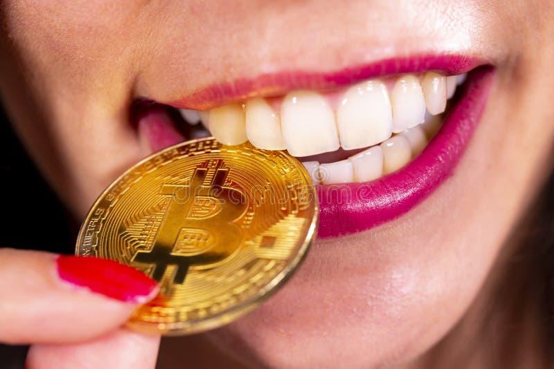 在妇女的嘴的Bitcoin硬币 免版税库存图片