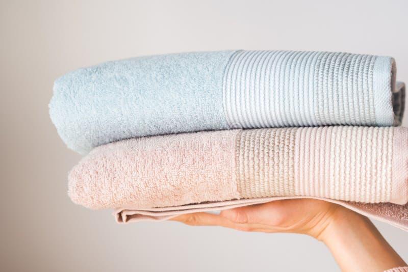 在妇女的手上的新鲜的毛巾在灰色背景 免版税库存照片