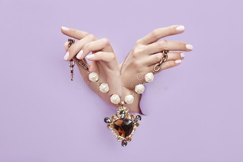 在妇女的手上的美丽的有镯子的首饰,手和项链从被撕毁的紫罗兰色紫色纸非常突出  库存图片