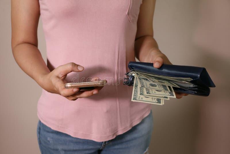 在妇女的手是有一团的bule皮革钱包一百美元和智能手机 免版税图库摄影