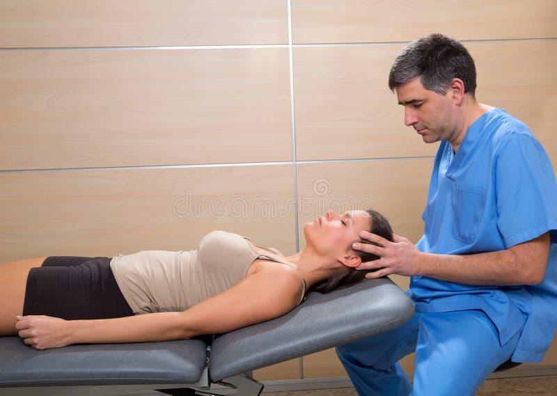 在妇女的头盖骨整骨疗法疗法医生手朝向 图库摄影