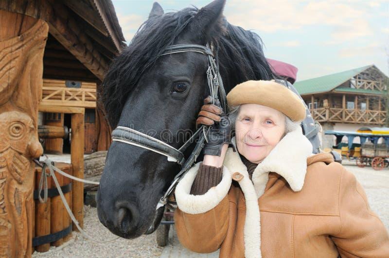 在妇女附近的愉快的马 免版税库存照片