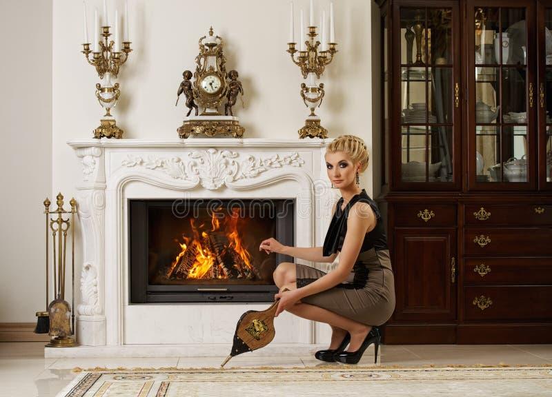 在妇女附近的美丽的白肤金发的壁炉 免版税库存照片