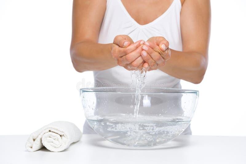 在妇女洗涤的手上的特写镜头在玻璃碗用水 免版税库存照片