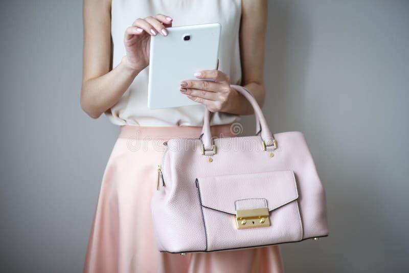 在妇女` s手上的数字式电子片剂 皮革浅粉红色的提包,夏天典雅式样 图库摄影