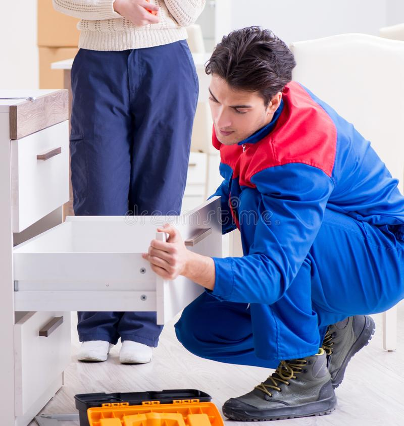 在妇女supervisio下的承包商安装工聚集的家具 库存图片