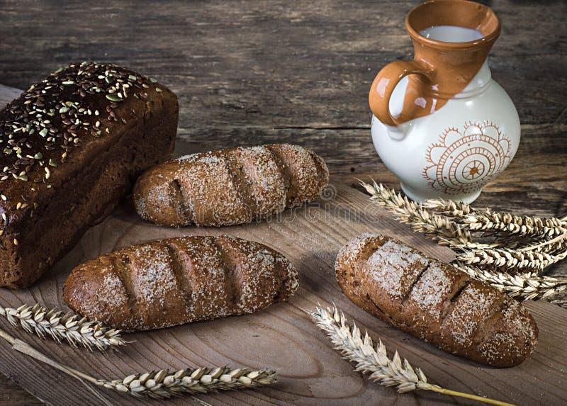 在委员会、葡萄酒刀子、牛奶、麦子剥落、坚果在桌上和老背景,概念的构成黑面包愈合 免版税图库摄影