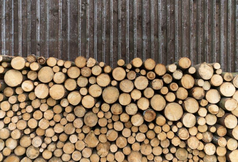 在委员会墙壁前面的柴堆 免版税图库摄影