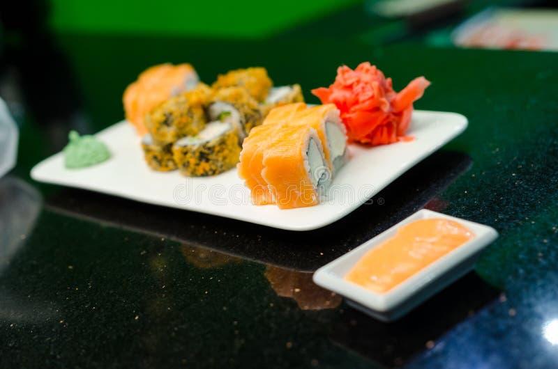 在委员会的费城卷经典黑暗的石头 三文鱼,费城乳酪,黄瓜,鲕梨 库存图片