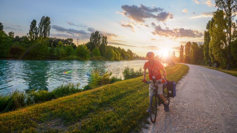在威尼托,日落的意大利供以人员骑自行车在沿Mincio河的石渣道路的山往曼托瓦 库存图片