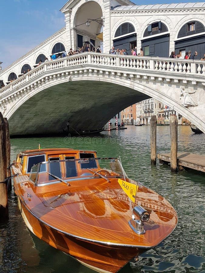 在威尼斯大石桥桥梁,威尼斯的一辆威尼斯式水出租汽车 图库摄影