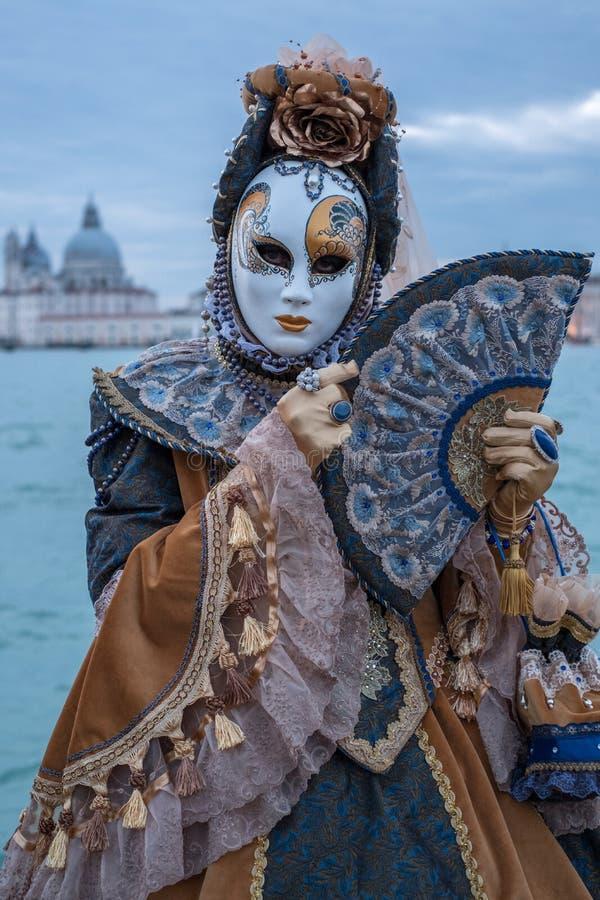 在威尼斯狂欢节期间,传统服装的与大教堂二圣玛丽亚della的妇女和面具在背景中向致敬, 免版税图库摄影