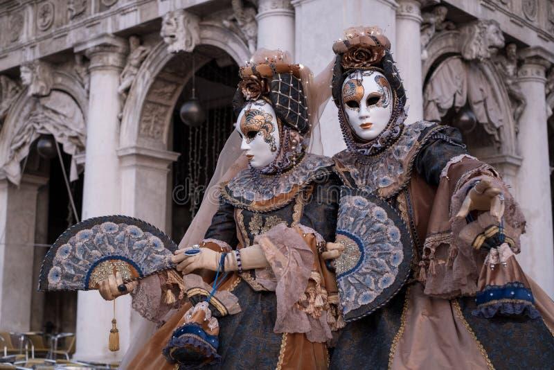 在威尼斯狂欢节期间,服装的被掩没的妇女,当装饰的爱好者,站立在曲拱前面在圣标记正方形 免版税库存图片